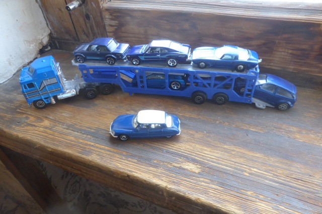 blue cars on a transporter